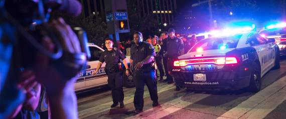 Bystanders stand near pollice baracades following the sniper shooting in Dallas on July 7, 2016.  A fourth police officer was killed and two suspected snipers were in custody after a protest late Thursday against police brutality in Dallas, authorities said. One suspect had turned himself in and another who was in a shootout with SWAT officers was also in custody, the Dallas Police Department tweeted.  / AFP / Laura Buckman        (Photo credit should read LAURA BUCKMAN/AFP/Getty Images)