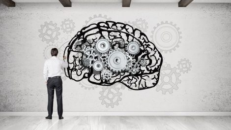 Rear view of businessman drawing giant brain sketch at concrete wall with gears. Concept of brain work