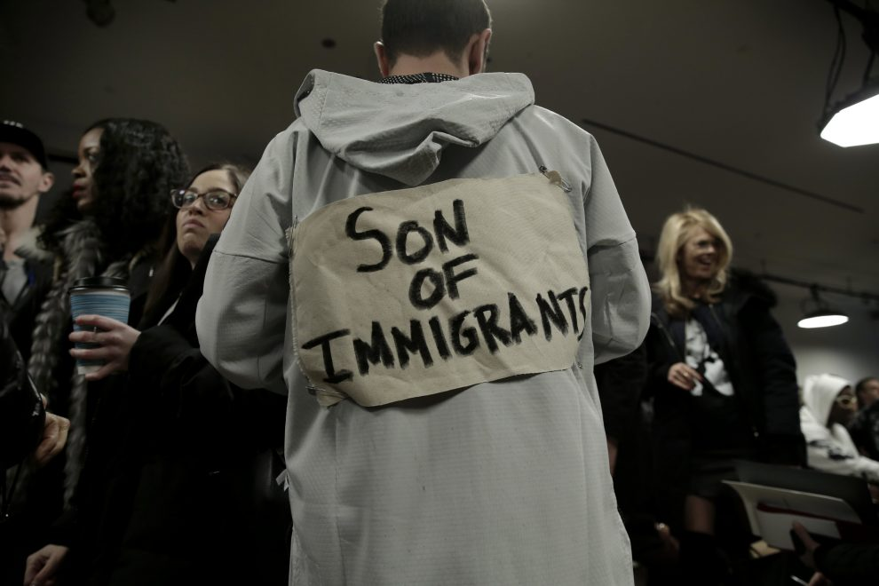 epaselect epa05789040 A guest wears sign on his back, 'Son of Immigrants' before the Public School fashion show at New York Fashion Week in New York, New York, USA, 12 February 2017. The Fall 2017 collections are being presented from 09 to 16 February.  EPA/PETER FOLEY