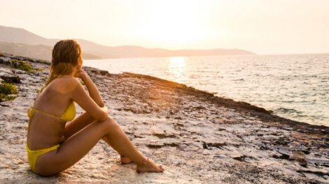 sunbathing-and-looking-at-romantic-sunset-picture-id928855726