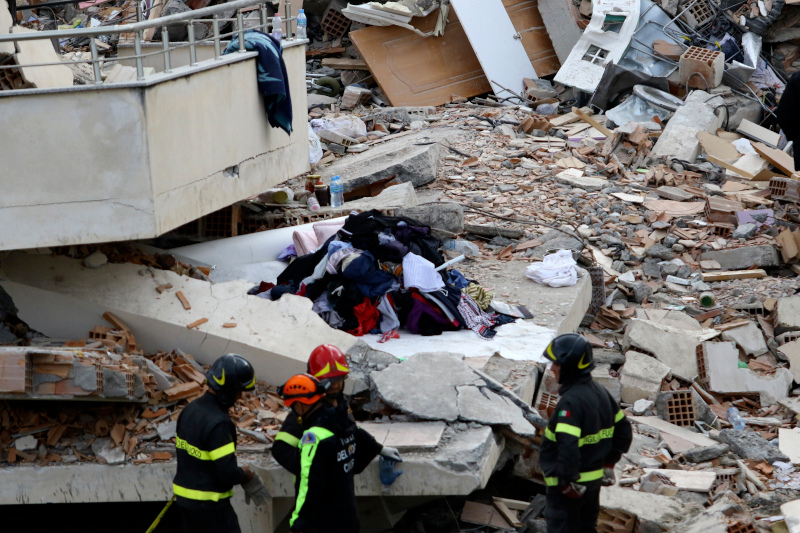 Italian rescuers stand in front of a collapsed house of Lala family in Durres, western Albania, Thursday, Nov. 28, 2019. Hopes were fading Thursday of finding anyone else alive beneath the rubble of collapsed buildings in Albania two days after a deadly quake struck the country's Adriatic coast, with the death toll increasing to 40 after more bodies were pulled from the ruins. (AP Photo/Hektor Pustina)